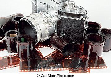 analog vintage SLR camera and color negative films on white