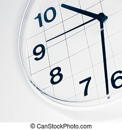 Analog wall clock, narrow focus on number nine, tinted black and white image