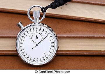analogue stopwatch with old books background