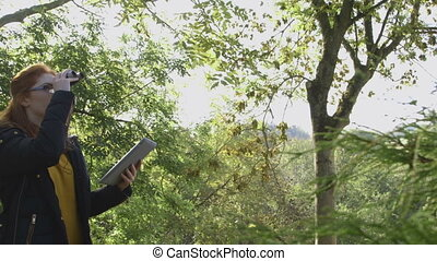 Analysing Nature with Binoculars - Young woman analysing...