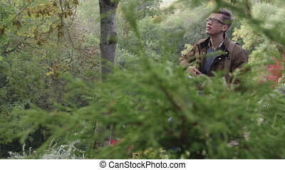Analysing Nature with Binoculars - Young man analysing...