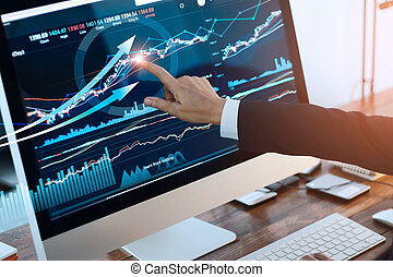 Analyzing data. Hand of businessman touching graph and chart stock market on screen in work place.