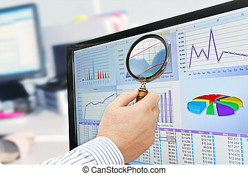 Male hand with magnifying glass over financial data and charts on computer screen