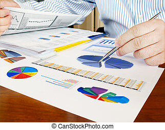 Analyzing investment charts. - Male hand with pen on the...