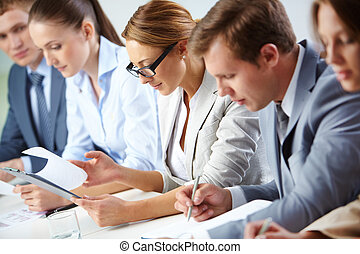 Analyzing progress - Female looking through business papers ...