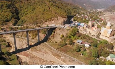 Ananuri castle complex and a modern, elevated highway bridge over a dry river bed in the Republic of Georgia, from an Aerial Perspective. 4k Ultra HD video