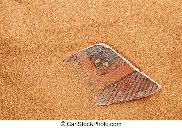 Anasazi pottery shard in red sand