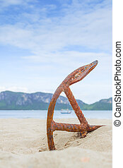 Anchor on the beach with mountains and sky background