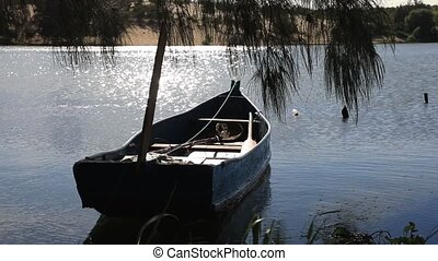 Anchored boat on the lake - Anchored boat on the shore of...