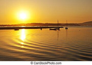 Anchored boats at sunset