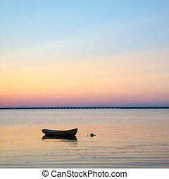Anchored rowboat at sunset