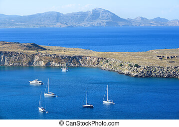 Anchored yachts and boats in blue sea bay with mountains in the distance