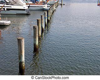 Anchoring poles in a marina