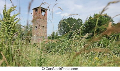 Ancient abandoned lookout tower overgrown among grass...