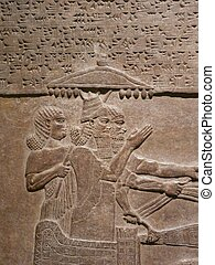 Ancient Assyrian wall carvings of men and cuneiform writing
