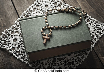 Ancient book and rosary on the table.