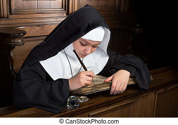 Ancient book and young nun - Young nun writing in an ancient...