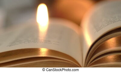 Ancient book lit by candles