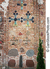 Ancient brick wall of The Kalozha church in Grodno, Belarus. Facade is decorated with majolica tiles and stones.