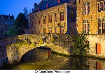 Ancient bridge at Dijver Canal in Bruges at night. (Belgium)...