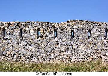 Ancient broken wall with little windows