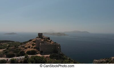 ancient brown stone fortress on rocky cliff against blue sea...