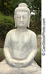 Ancient Buddha statue against green woods