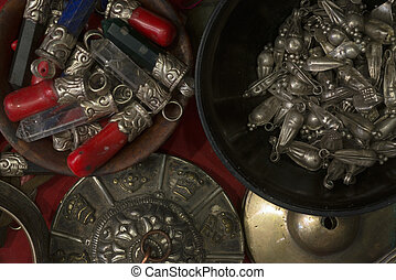 Ancient Buddhist decorations, metal beads in bowl, red crystals of stone, quartz, metal religious objects.