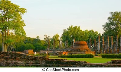 Video 1080p - Ancient Buddhist temple ruin in Sukhothai Thailand. Foundations, columns, and some complete spires and sculptures can be seen amongst an immaculately landscaped park.