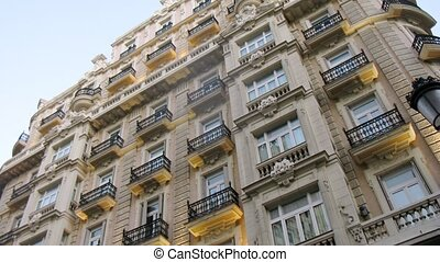 Ancient building with balconies stands against blue sky,...