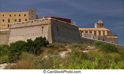 Medium low-angle till shot of a historical high brick wall buildings with wind towers, Ibiza, Spanish Island, Spain