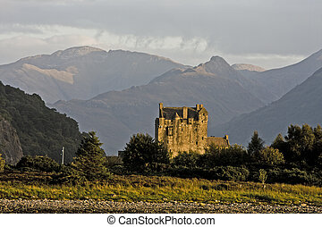 ancient castle in scotland with forest and mountains in...