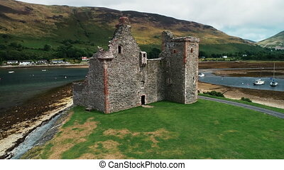 Ancient castle ruins aerial shot on Loch Ranza bay. Historical monument and heritage of British culture. Amazing scenery on Arran Island, Scotland, UK, Europe. Footage view