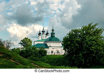 Ancient Church of the Entrance to Jerusalem and Pyatnitskaya Church, Suzdal. View from the hill in summer on a cloudy day