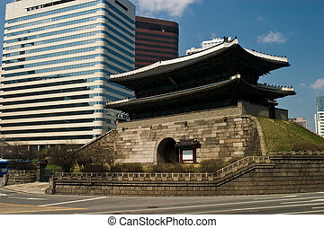 600 year old pagoda style gate sits below modrn skyscrapers in downtown Seoul.