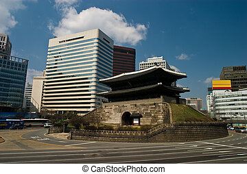 Street circles 600 year old pagoda style gate in central Seoul with modern buildings.