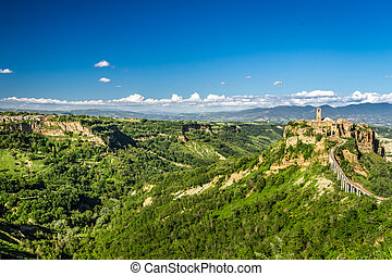 Ancient city on hill in Tuscany on a mountains background