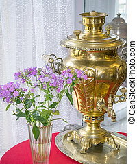 Ancient device for making tea and vase of flowers by the window.