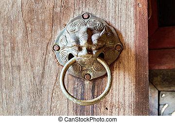 Ancient door handle on wooden door