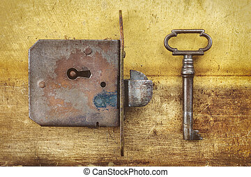 Ancient weathered door lock with key on a metal background