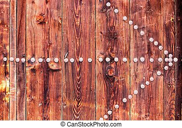 Ancient door with rusty nails in the form of an arrow