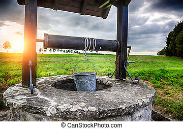 Ancient draw-well in European village at summertime