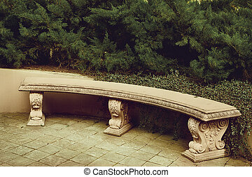 ancient empty marble bench under a green plant in the park