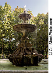 Ancient fountain in a square surrounded by trees