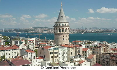 Ancient Galata Tower in Center of Istanbul on clear Blue Sky Day, Crane Shot up revealing Bosphorus River