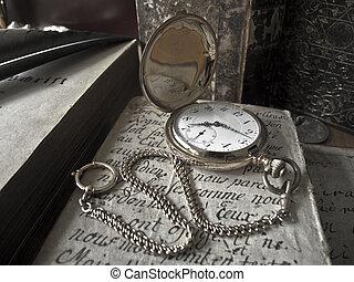 ancient golden pocketwatch lying on an antique handwritten sheet of paper