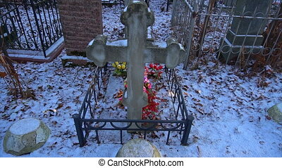 ancient grave cross with artificial flowers.