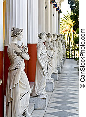 Ancient Greek statues standing outside a classic era temple