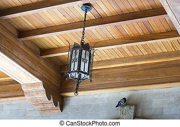 Ancient hanging lamp on ceiling of old wooden house