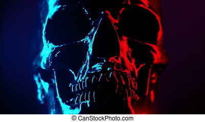 Ancient human skull head rotating close-up. Neon turquoise and red light. Spooky and sinister. Glamour, disco, halloween concept.